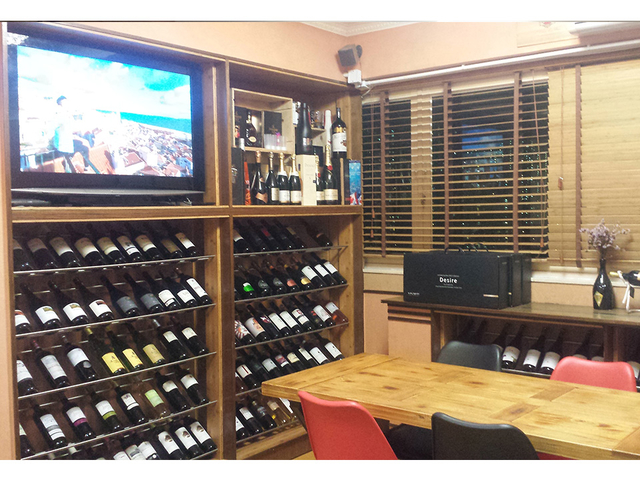 full rack with selection of wines and tv screen at the top of the rack