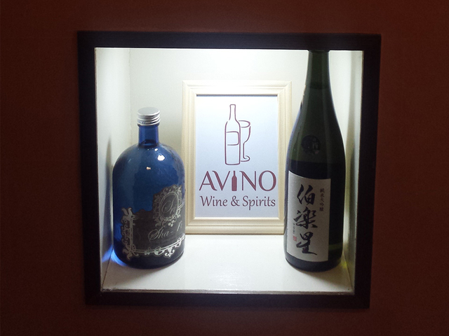 wine bottle display together with a frame of avino's logo