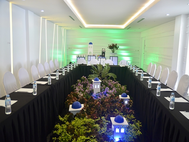 private meeting room with white interior and long black table