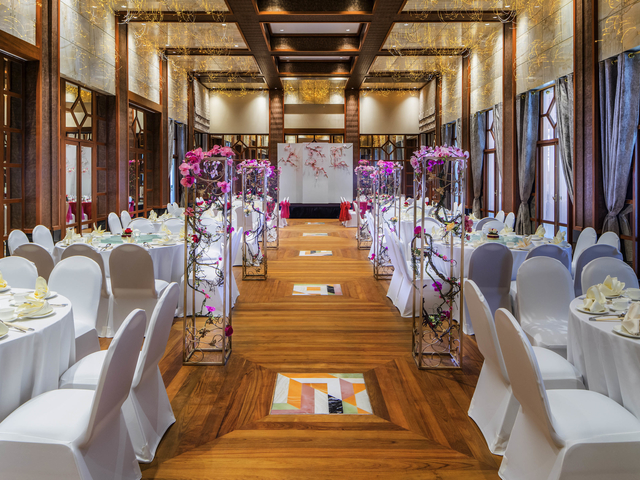 high ceiling function room decorated with simple flowers and round dining tables