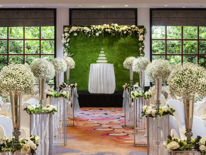 wedding aisle decorated with white flowers and green background on the stage