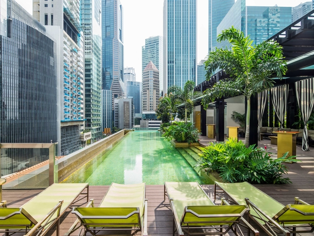 infinity edged rooftop pool bar with city view