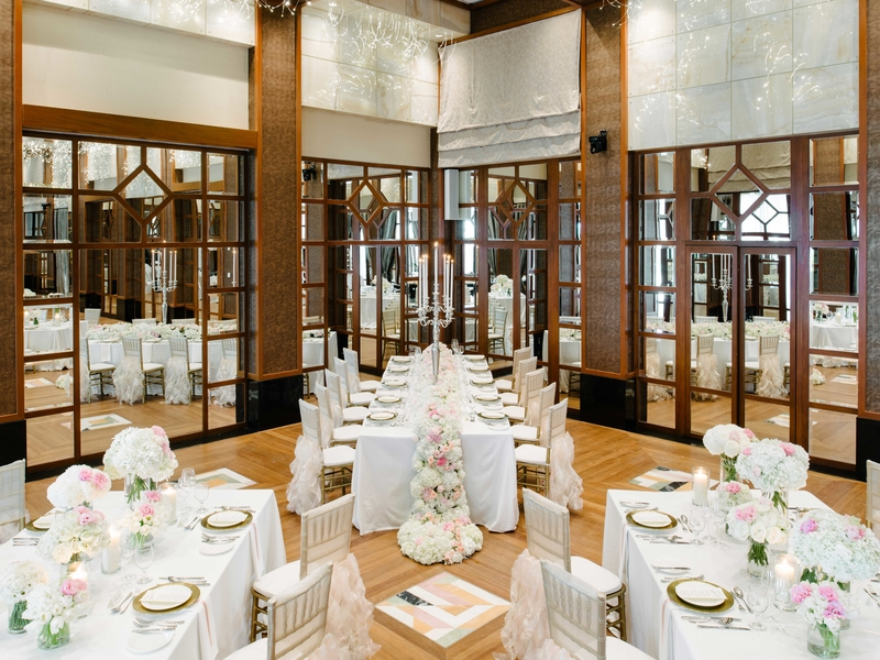 singapore ballroom with large mirror wall and long white tables decorated with flowers