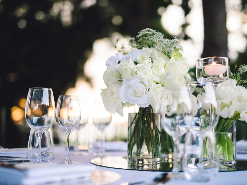 white themed wedding dining table decorated with flowers vase
