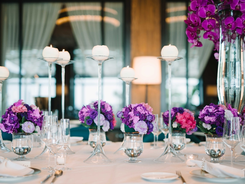 dining table decorated with candle and purple flower