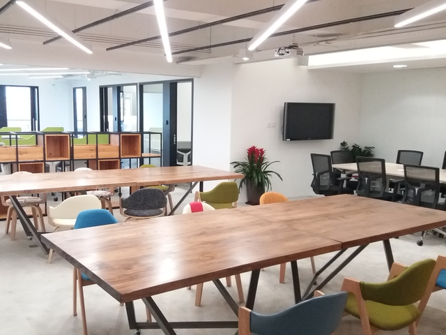 coworking space area usin long wooden table and colourful chairs