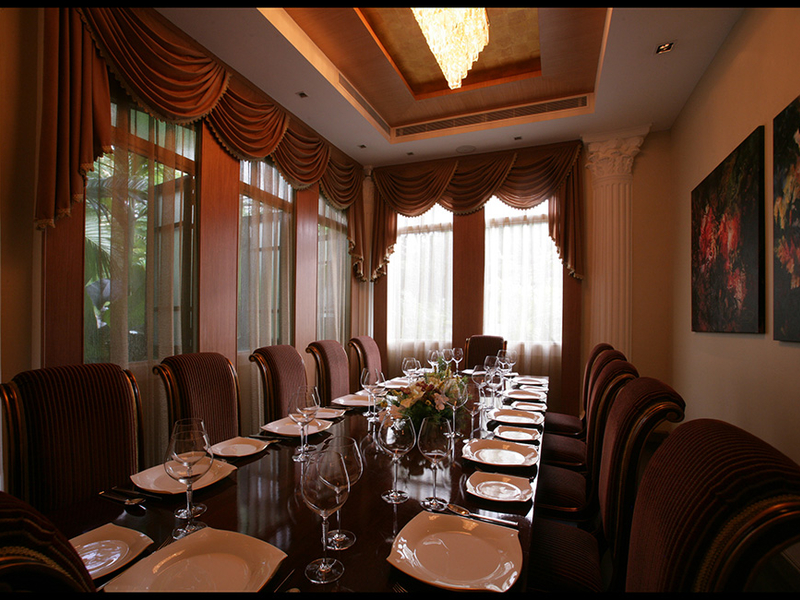 private room in indian restaurant with long dining table and large windows