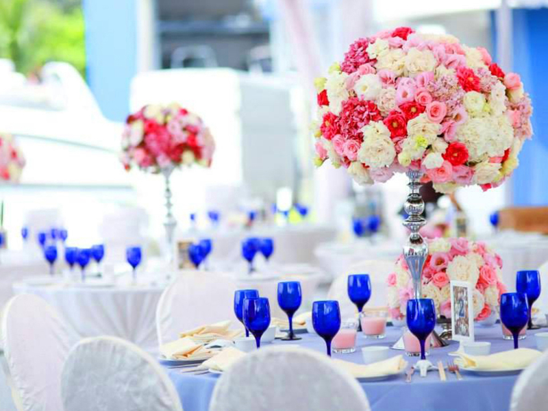 table decorated with standing colourful flower and blue glass