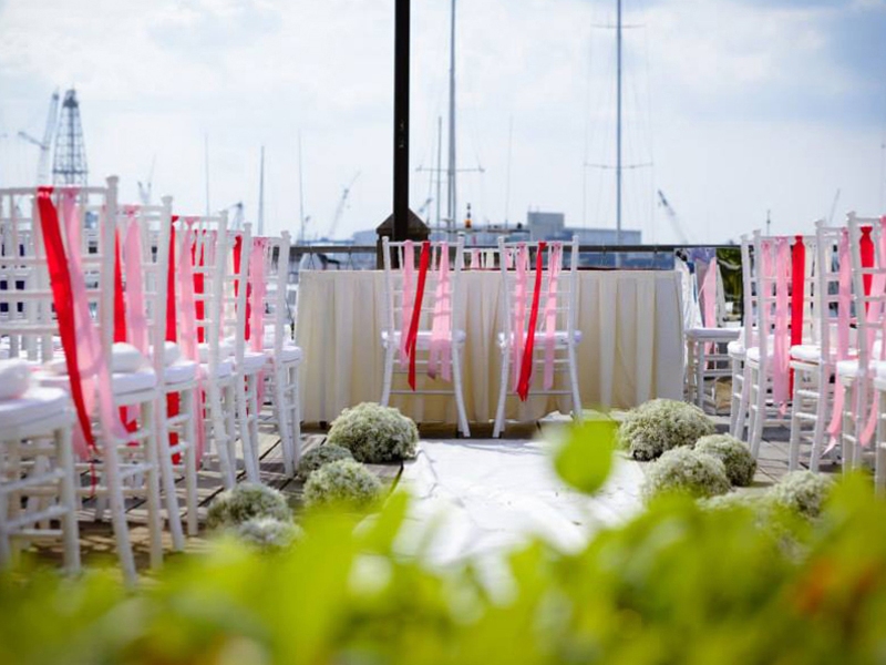 outdoor solemnisation with white chairs decorated with red ornament