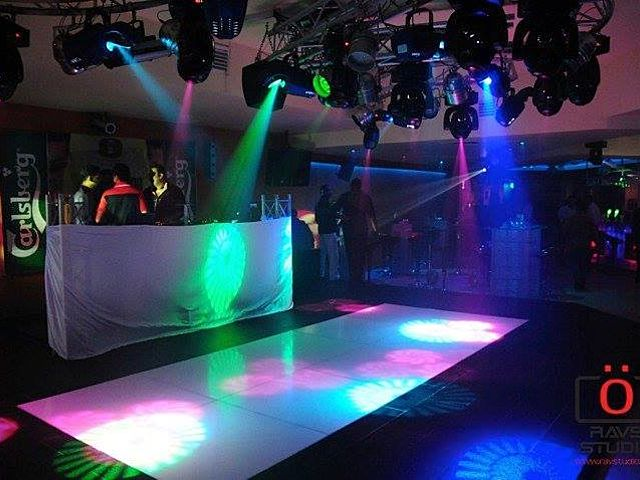 dance floor in font of DJ booth with colourful lighting