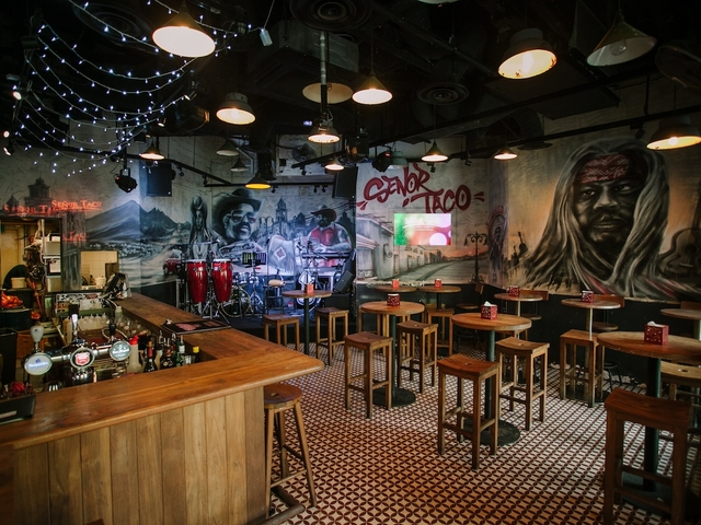 wooden interior bar in singapore with wall murals and patterned floors