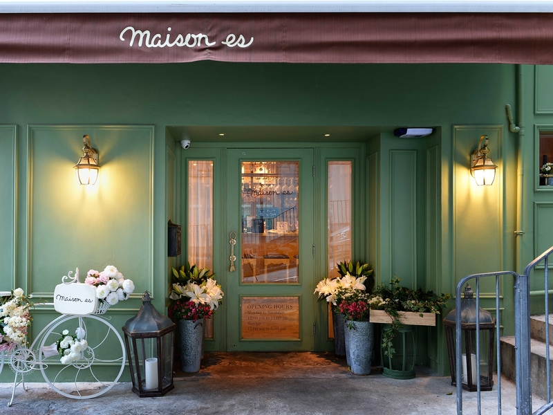 entrance to restaurant featuring bicyle and flower vases