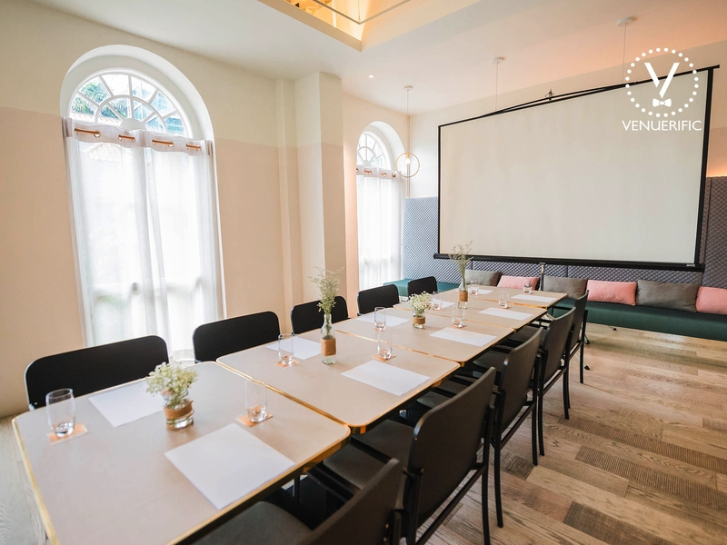 pastel themed meeting room with long table and projector screen