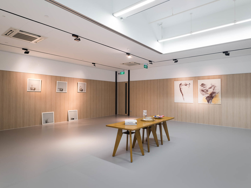 high ceiling gallery in singapore with track lights and wooden table