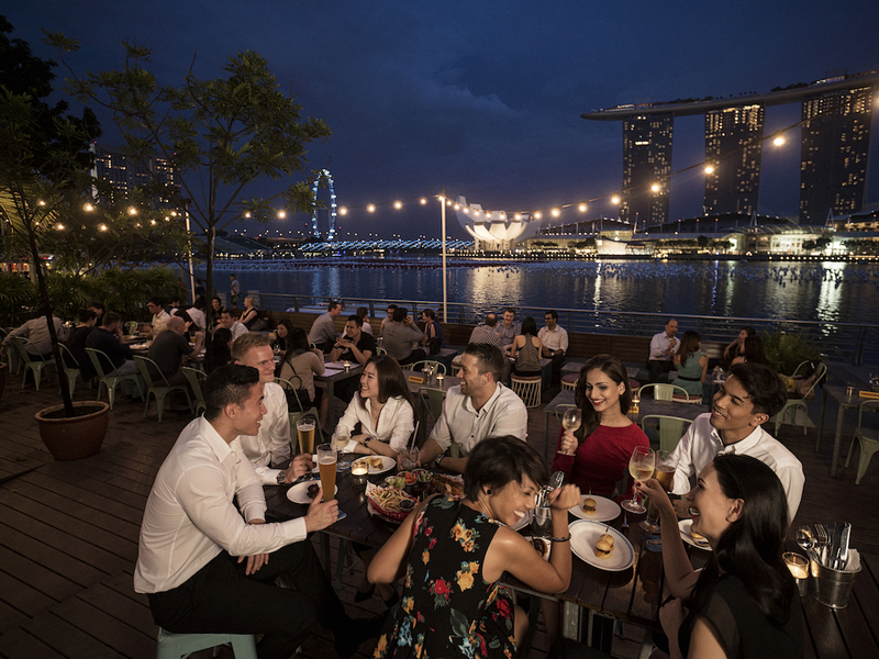 friends enjoying dinner together at outdoor restaurant with city view