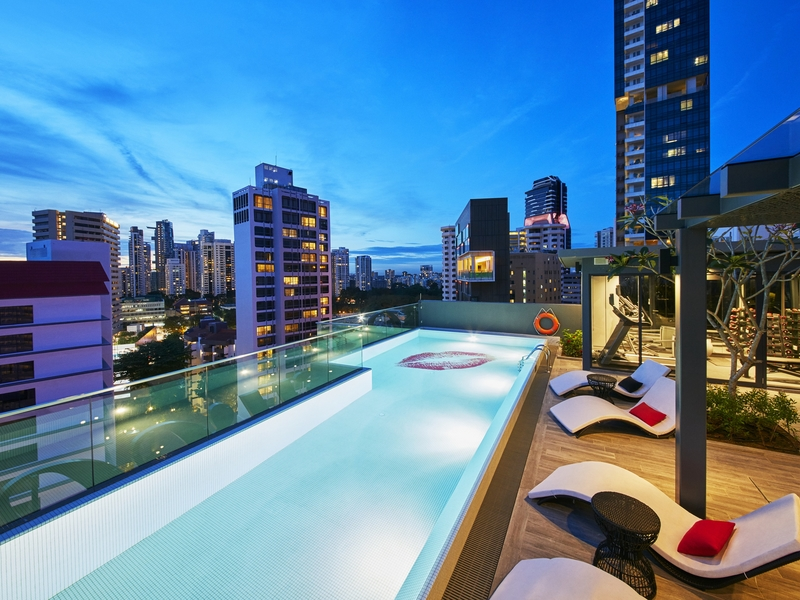 outdoor pool during night time with city view