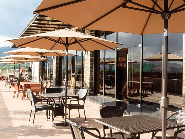 rooftop area with natural sunlight and seating area under the umbrella