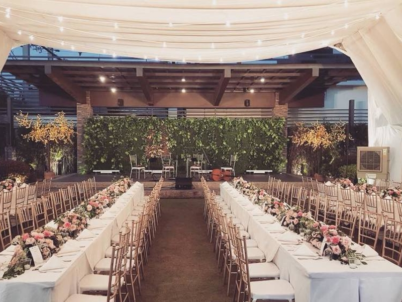 rows of dining tables decorated with flowers; centre stage