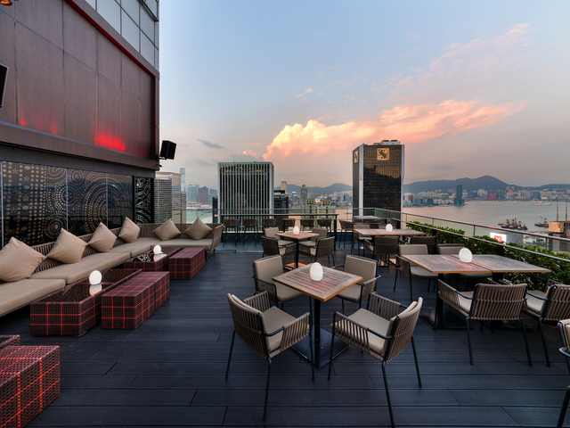 rooftop bar area with sofa table and table chair setting