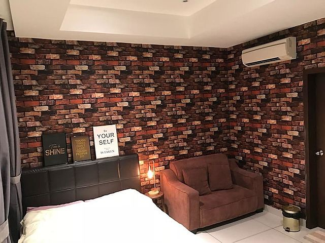 bedroom with bricks wallpaper and sofa beside the bed