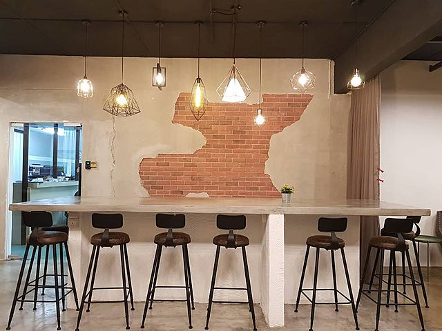 long high table with high chairs with brick wall