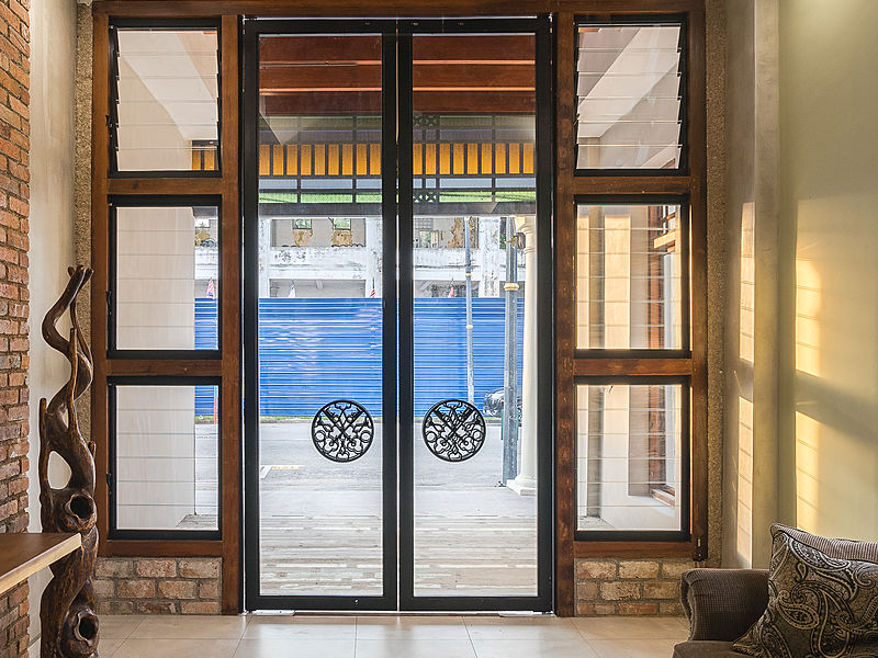 treasures hotel and suites malacca entrance with glass door and brick wall