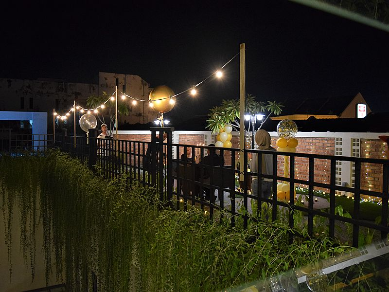 people sitting in a rooftop garden venue malacca with fairy lights