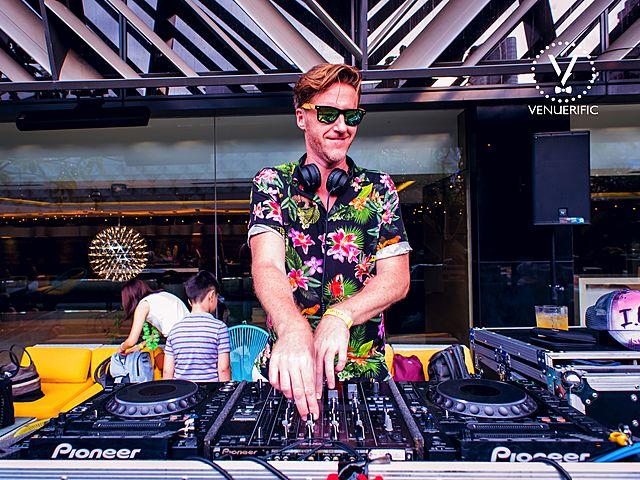 dj performance at outdoor bar using sunglass and hawaiian shirt