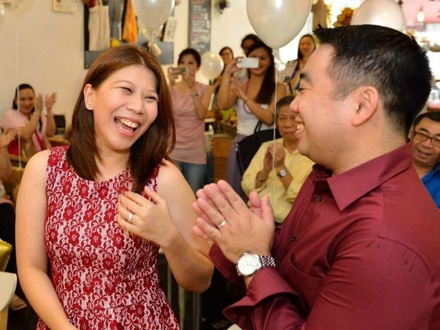 men and women are laughing and taking photos during birthday party celebration