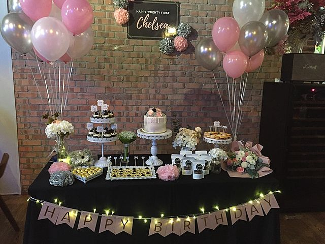 pink birthday theme table decor with cake and balloon