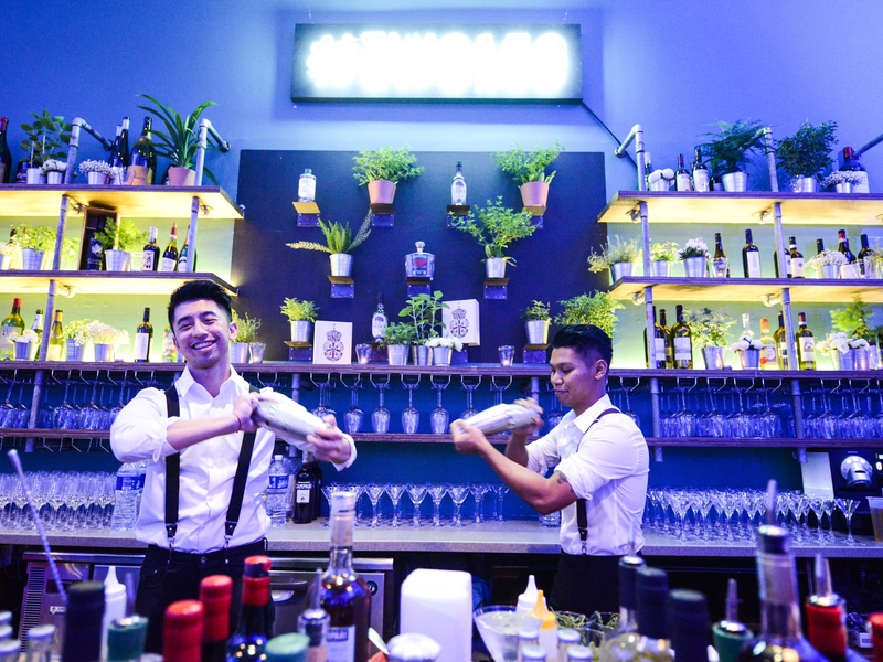 two bartenders are shaking the cocktails in the bar