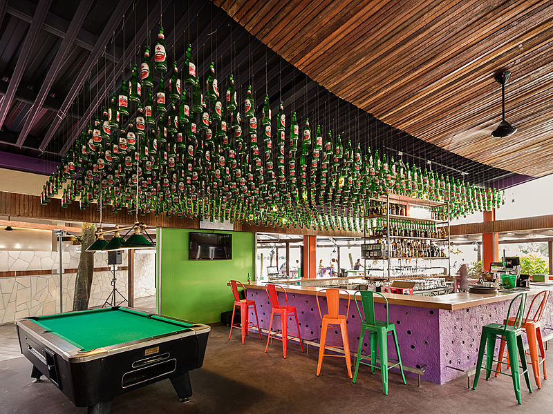 indoor venue with pool table and beer bottles hanging at the top of the bar
