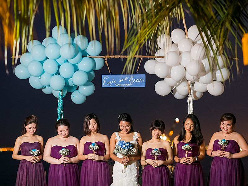 bride and 6 bridesmaid with purple long dress holding white blue flowers