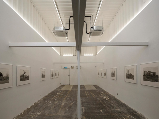 indoor gallery with 2 projectors hanging at the ceiling