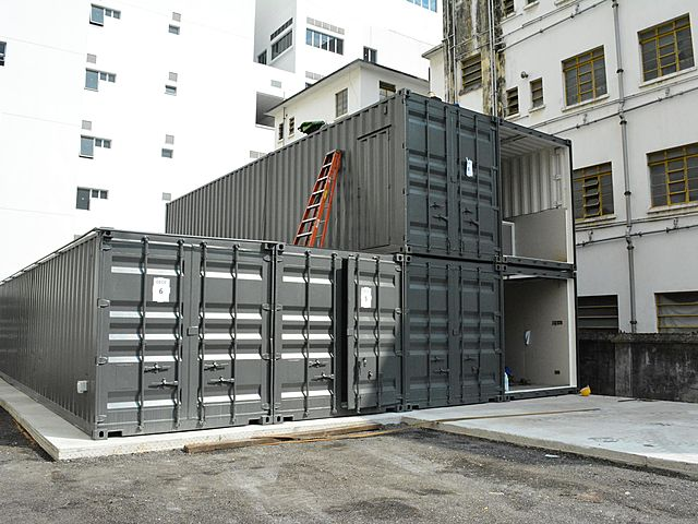the closer look of shipping containers with red stairs
