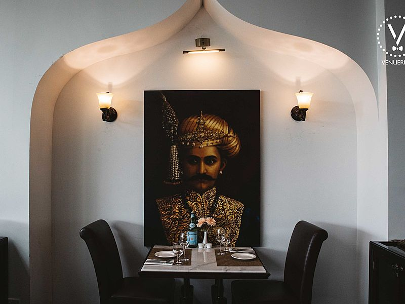 one of the dining area with indian painting and lighting on the wall