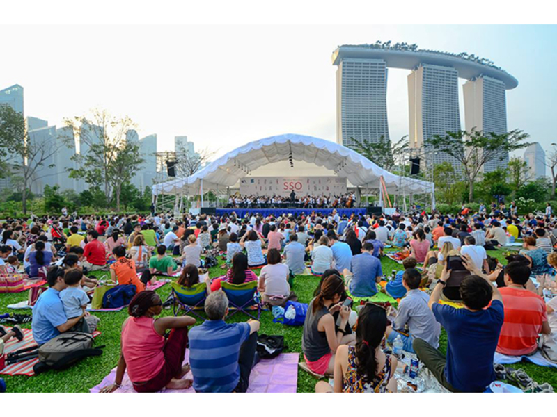 people enjoying performance at garden area with the view of marina bay sands