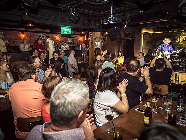 pub visitor enjoying live music night in hero's singapore pub