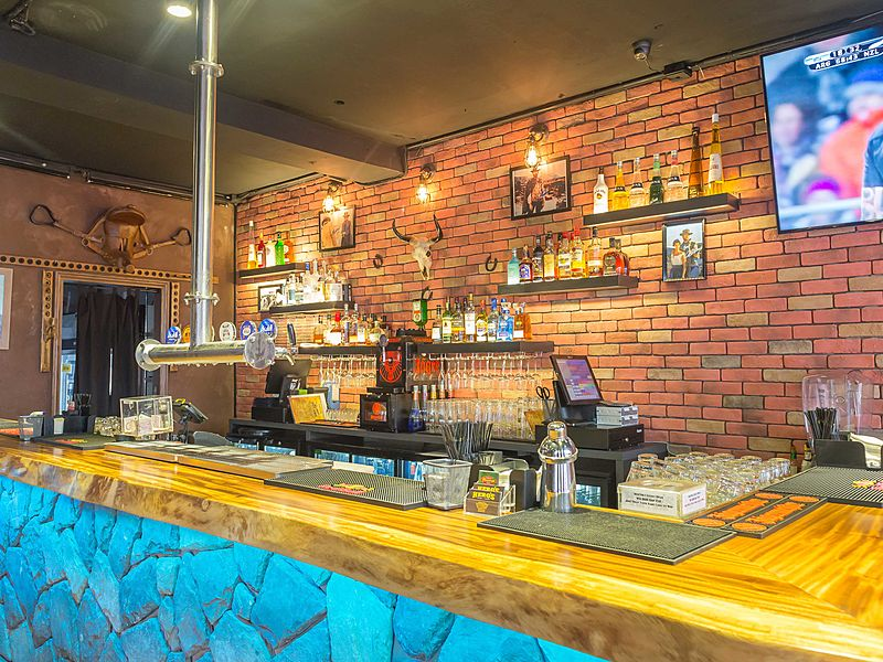 small bar with wood table and brick background