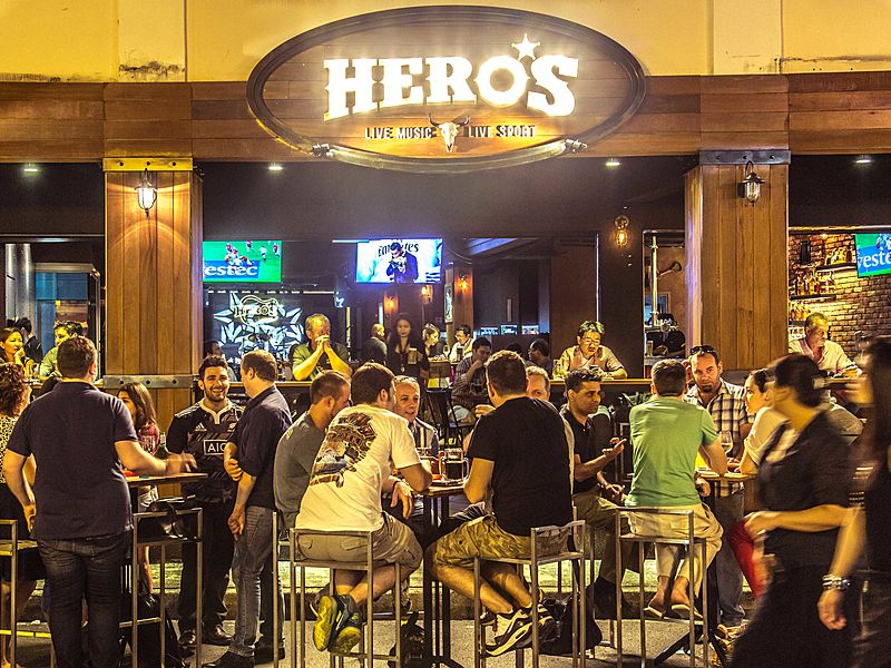 visitor enjoying live music in hero's pub singapore at night