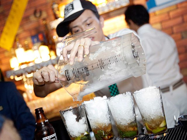 bartender with hat serving drink for customers