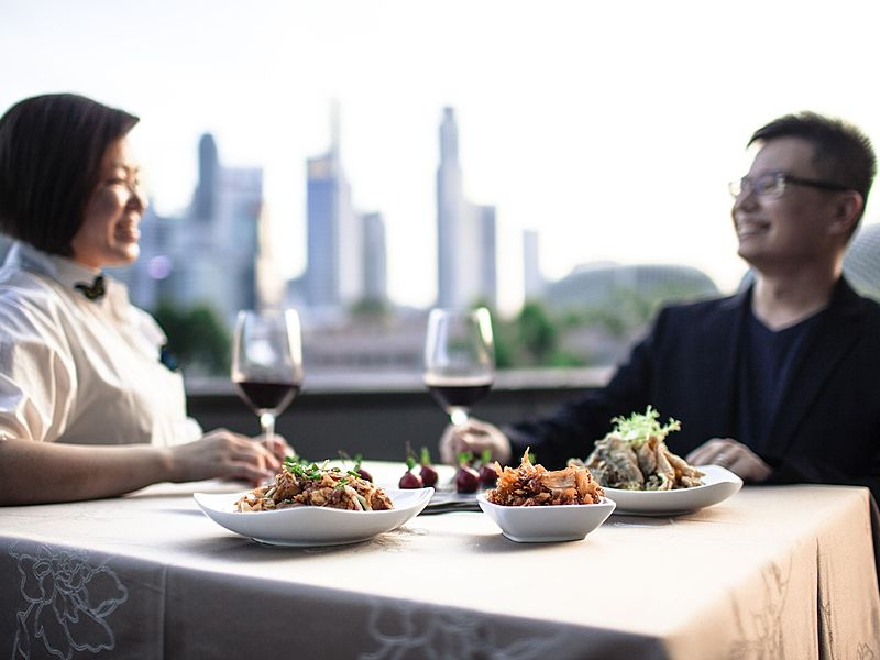 two people enjoying brunch on rooftop with city view