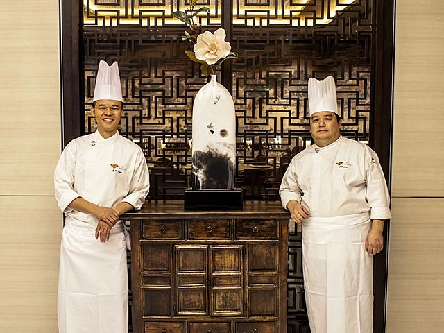 two chefs standing together with chinese ornament's background