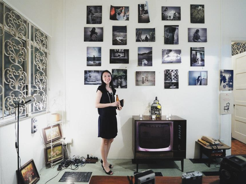 girl with black dress standing in font of old family photos