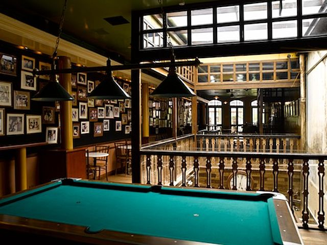 billiard table in the second floor bar with photo frame at the walls