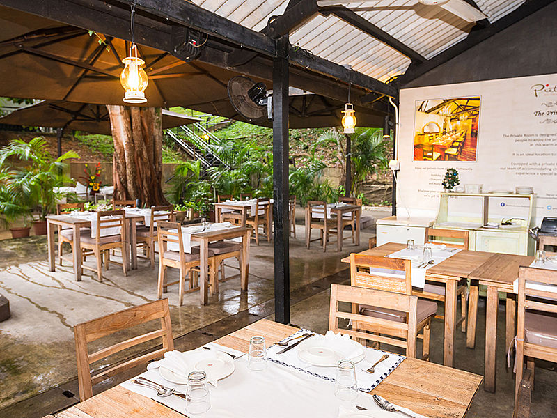 semi-outdoor restaurant with wooden interior and garden view
