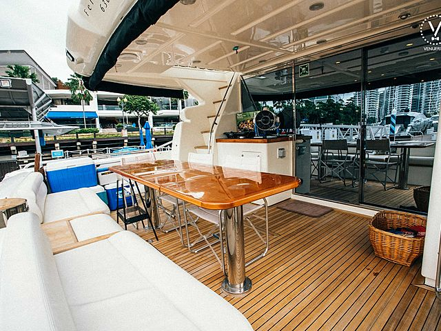 yacht stern equipped with a long white couch and dining table