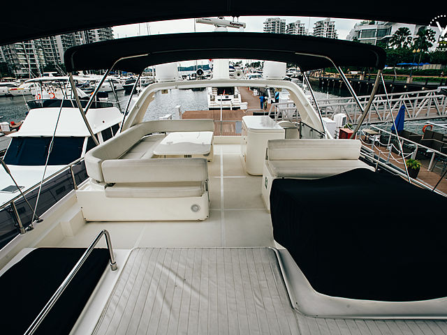yacht upper deck area with black roof tent and some white couches