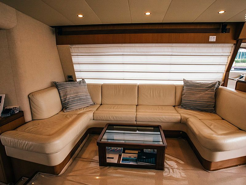 beige round couch and mini glass table in yacht cabin room