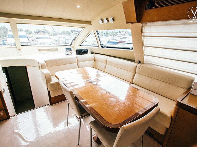 yacht lower cabin area with long couch and wooden table